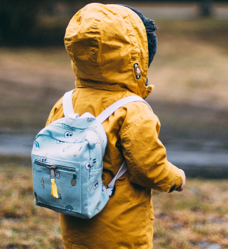child with raincoat and small backpack on