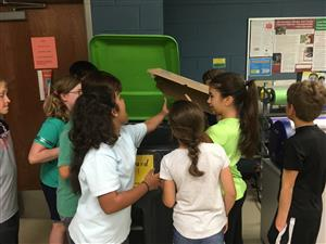 student teaching recycling cardboard to other students