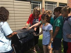 teacher showing students how to compost