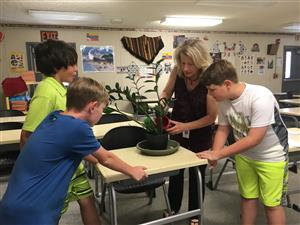 Teacher teaching students how to care for plants