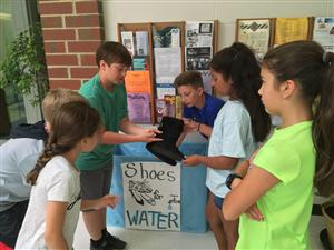 students teaching other students how to recycle shoes