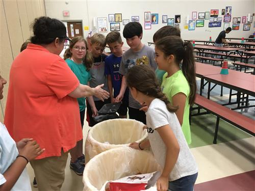 staff member teaching students how to recycle styrofoam