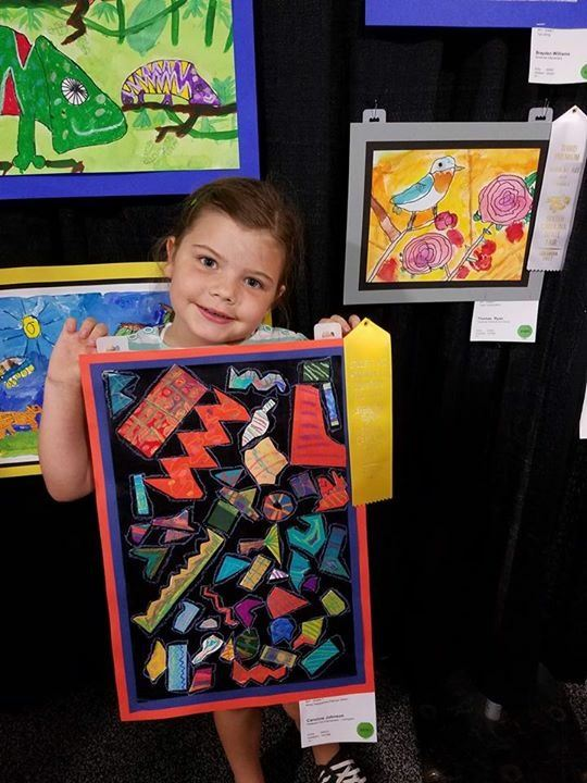 student showing winning artwork